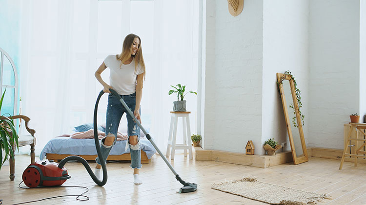 vacuum cleaning living room during spring clean